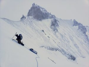 climber and sled on snow slope