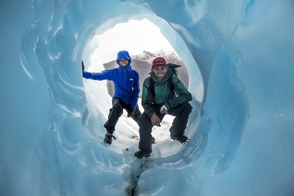 Glacier hikers exploring a newly-formed ice tunnel on a late season hike!