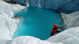 glacier ice climber with blue pool