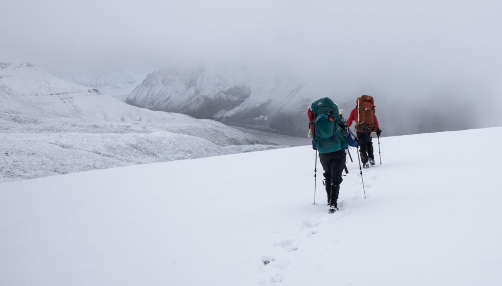 Hiking Over a Snowy High Pass